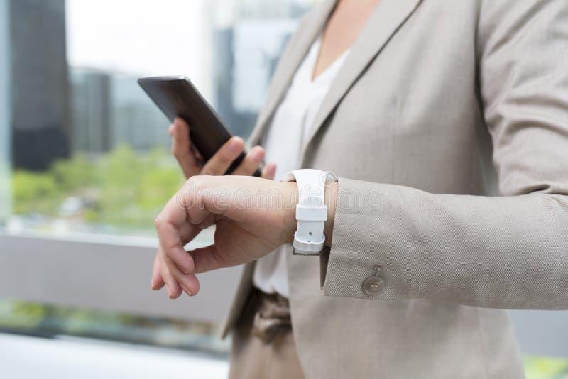 Frau mit Handy schloss an eine intelligente Uhr an stockfotos