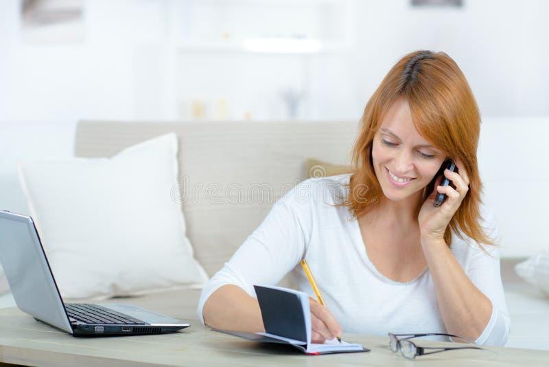 Frau mit Handy Verabredung im Tagebuch notierend stockbilder