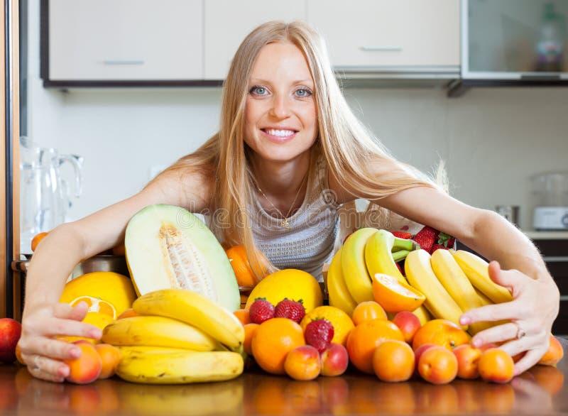 Frau mit Haufen von Früchten stockbild