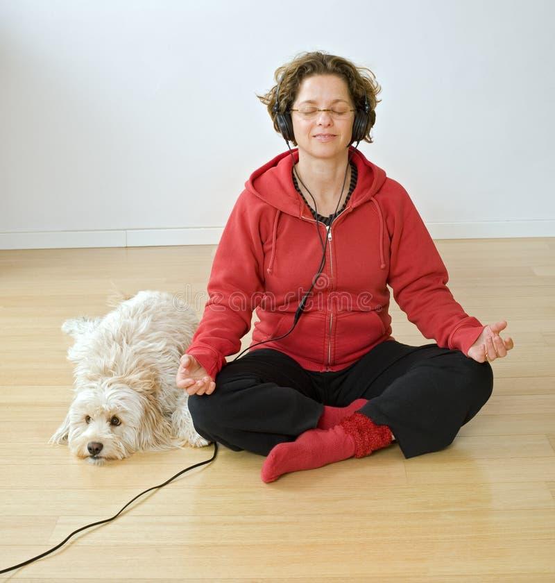 Frau mit headphons und Hund stockbilder