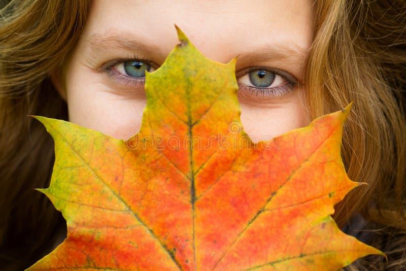 Frau mit Herbstblatt stockfotos