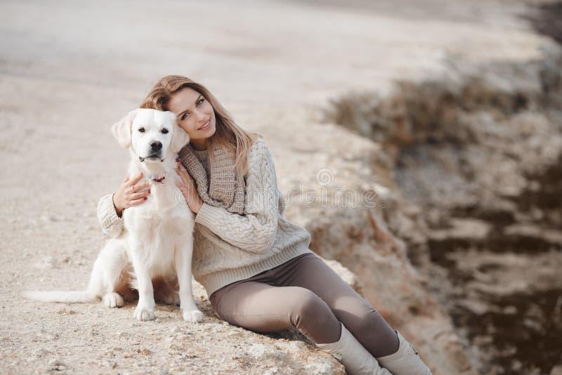Frau mit Hund auf dem Seeufer lizenzfreies stockfoto