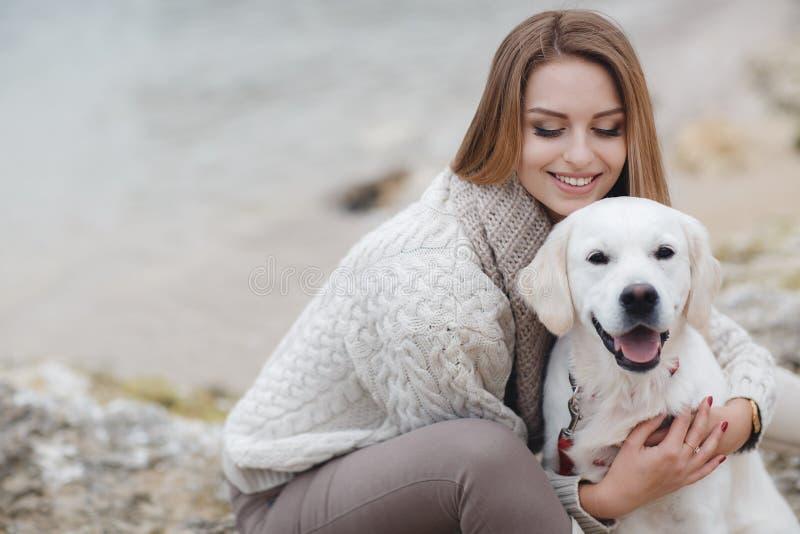 Frau mit Hund auf dem Seeufer stockbilder