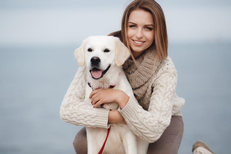 Frau mit Hund auf dem Seeufer lizenzfreie stockfotos