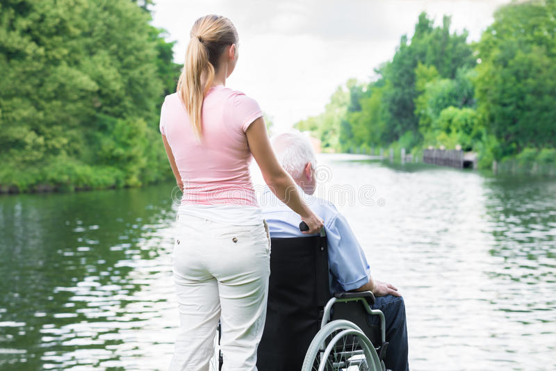 Frau mit ihrem behinderten Vater On Wheelchair Looking am See lizenzfreie stockfotografie