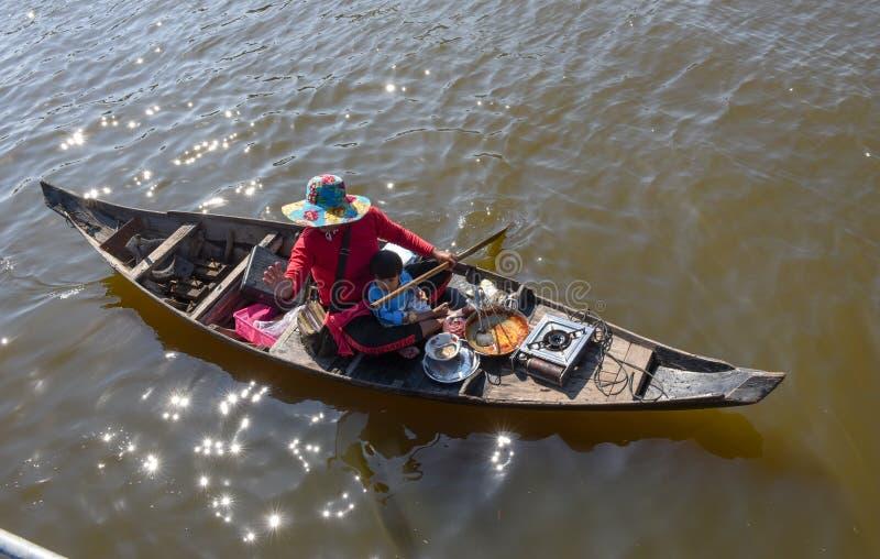 Frau mit ihrem Sohn auf einem Kanu am Tonle Sap See lizenzfreie stockfotos