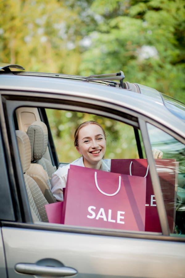Frau mit ihren Einkaufstaschen in das Motor- Einkaufskonzept lizenzfreie stockfotos