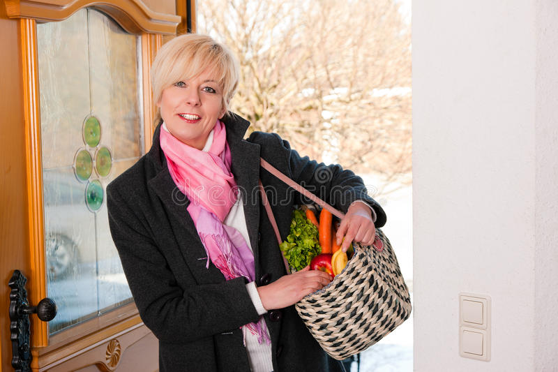 Frau mit ihren Lebensmittelgeschäften stockfotografie