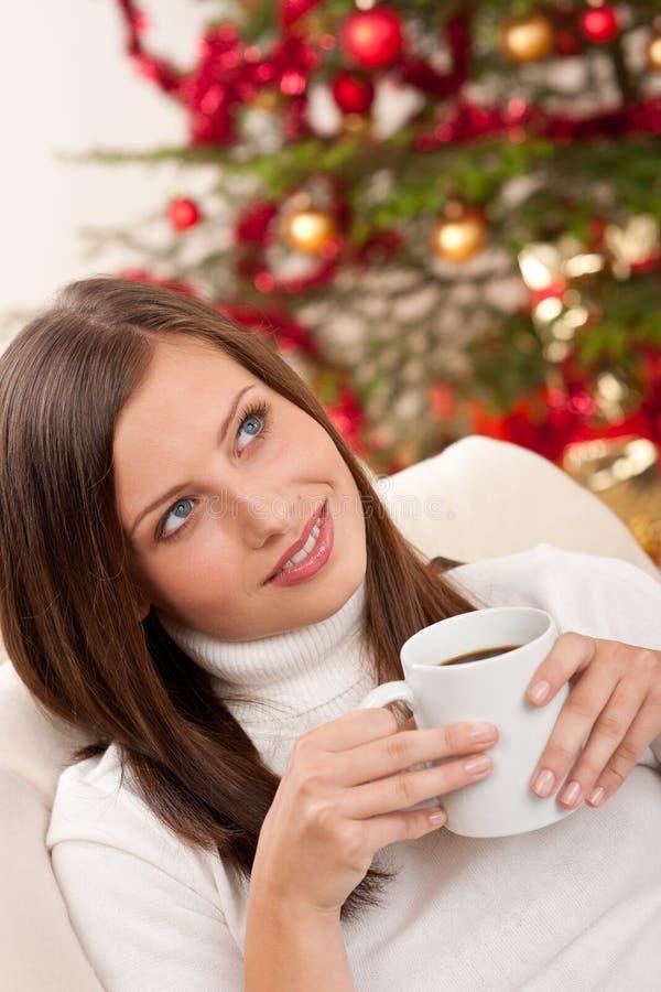Frau mit Kaffee vor Weihnachtsbaum lizenzfreies stockbild