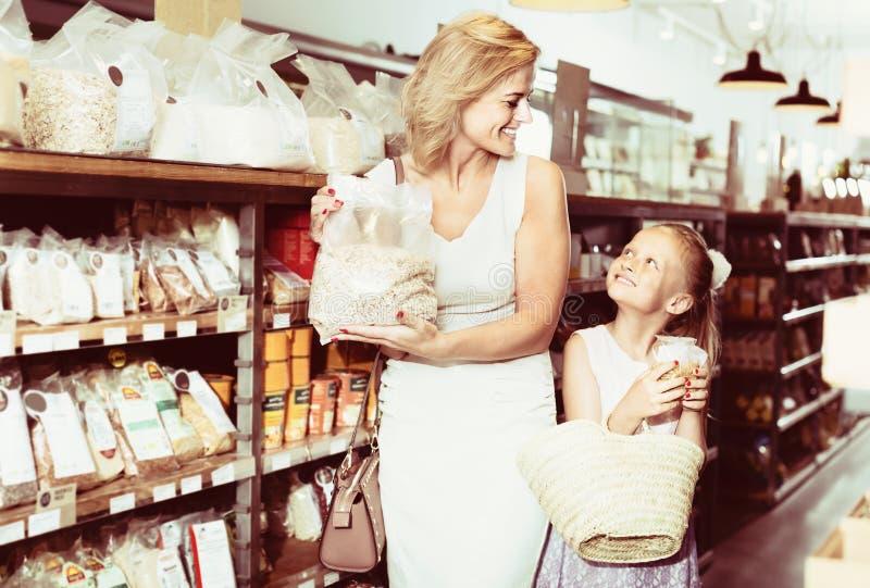 Frau mit kaufenden Getreide der Tochter im Speicher lizenzfreies stockbild