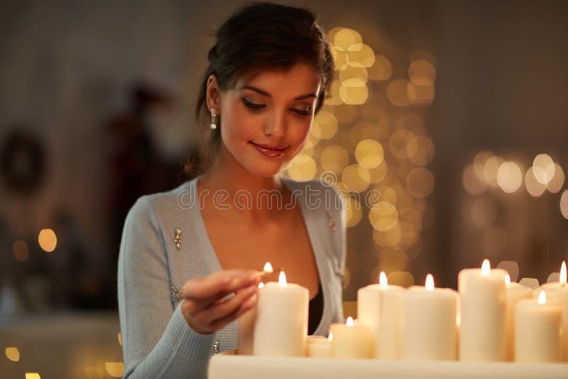 Frau mit Kerzen, Kamin, Weihnachtslichter stockbild