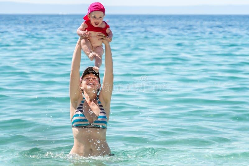 Frau mit Kind über ihrem Kopf im Meer stockbild