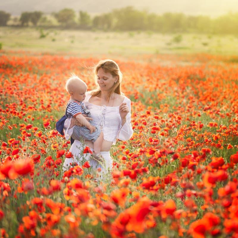 Frau mit Kind auf dem Gebiet mit Mohnblumen lizenzfreie stockfotos