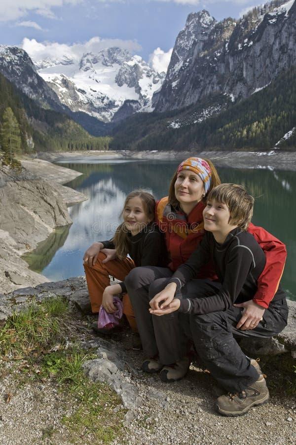 Frau mit Kindern in einem See in den Bergen stockbild