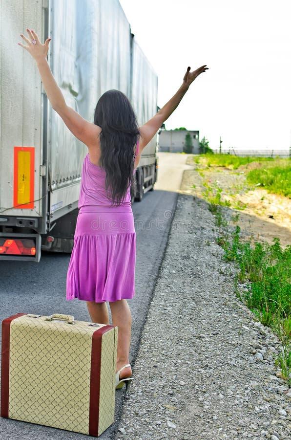 Frau mit Koffer trampend