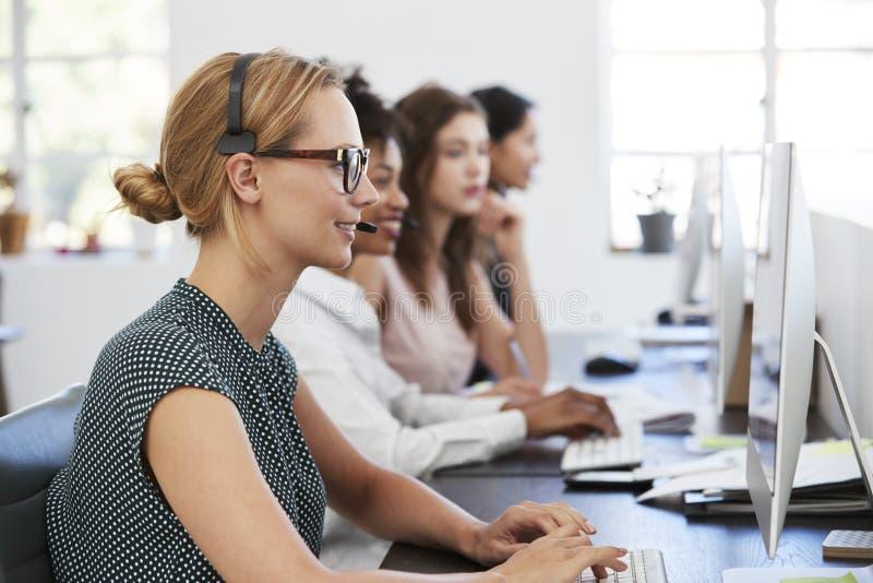 Frau mit Kopfhörer am Computer im Büro neben Kollegen lizenzfreies stockbild