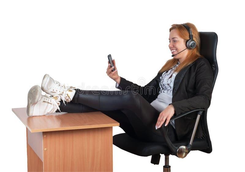 Frau mit Kopfhörer, smarthone und den Beinen auf dem Schreibtisch stockfotos
