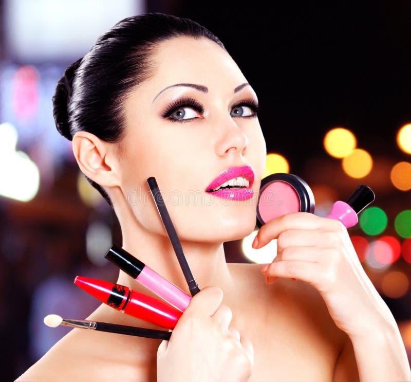 Frau mit kosmetischen Werkzeugen des Makes-up nähern sich ihrem Gesicht. stockbilder