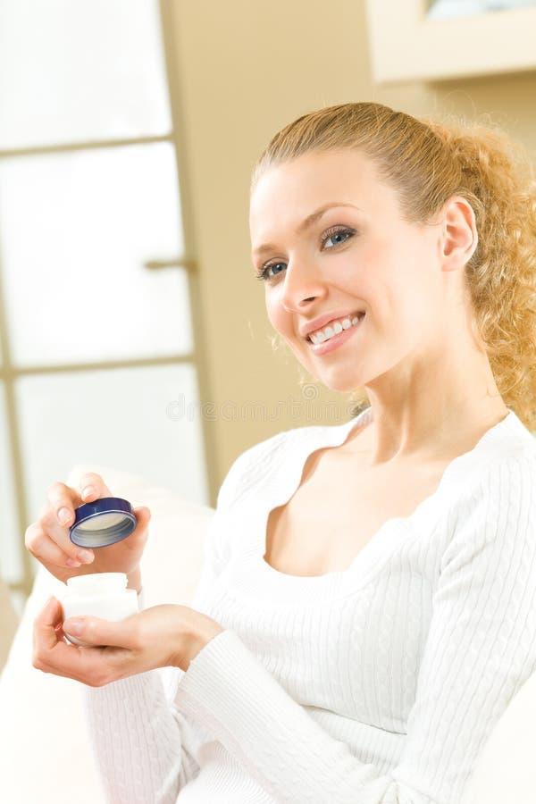 Frau mit kosmetischer Sahne lizenzfreie stockbilder