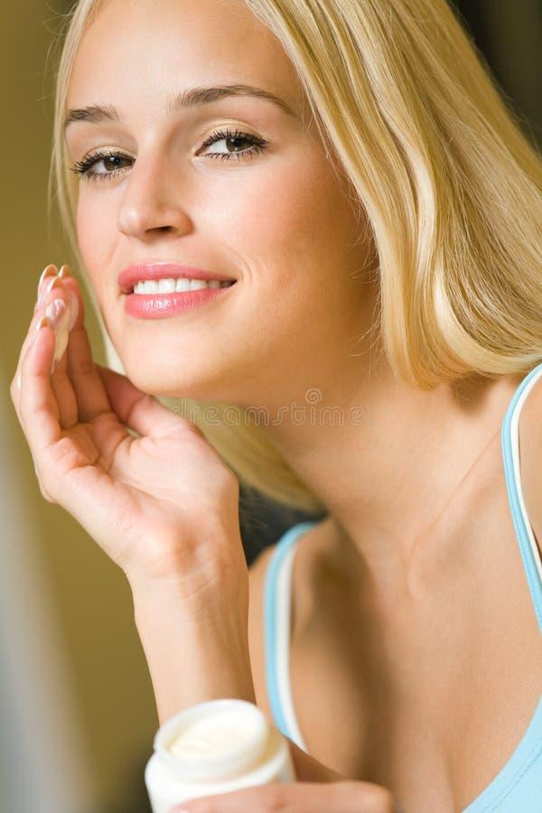 Frau mit kosmetischer Sahne stockbilder