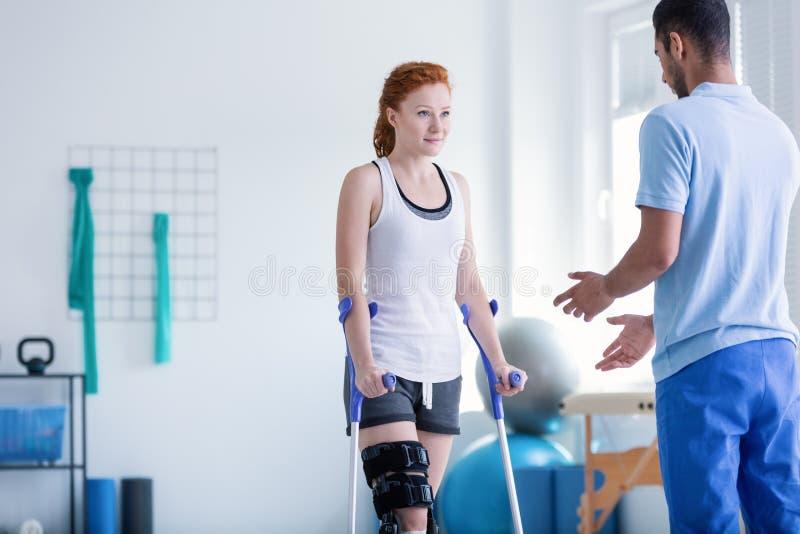 Frau mit Krücken während der Rehabilitation stockbild