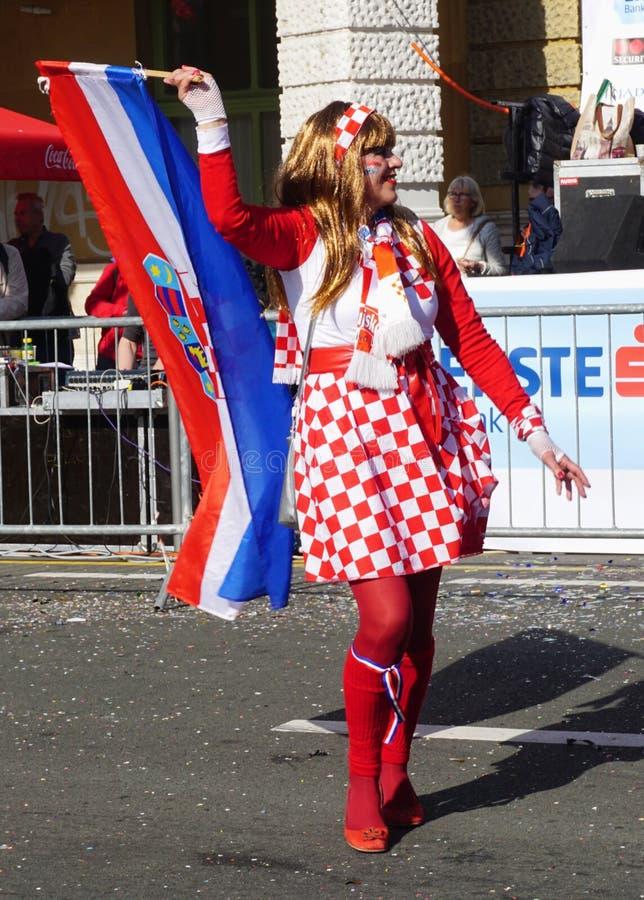 Frau mit kroatischer Flagge und im Kostüm mit dem kroatischen nationalen Muster gekleidet, das auf der Straße am Karnevalstag auf lizenzfreie stockbilder