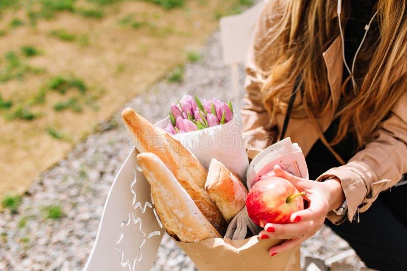 Frau mit langer Haarholdingeinkaufstüte mit Käufen und roter geschmackvoller Apfel auf dem Unschärfehintergrund M?dchen mit Rot lizenzfreies stockfoto