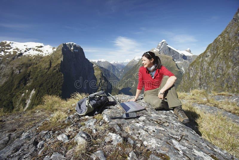 Frau mit Laptop auf Boulder gegen Berge stockfotos
