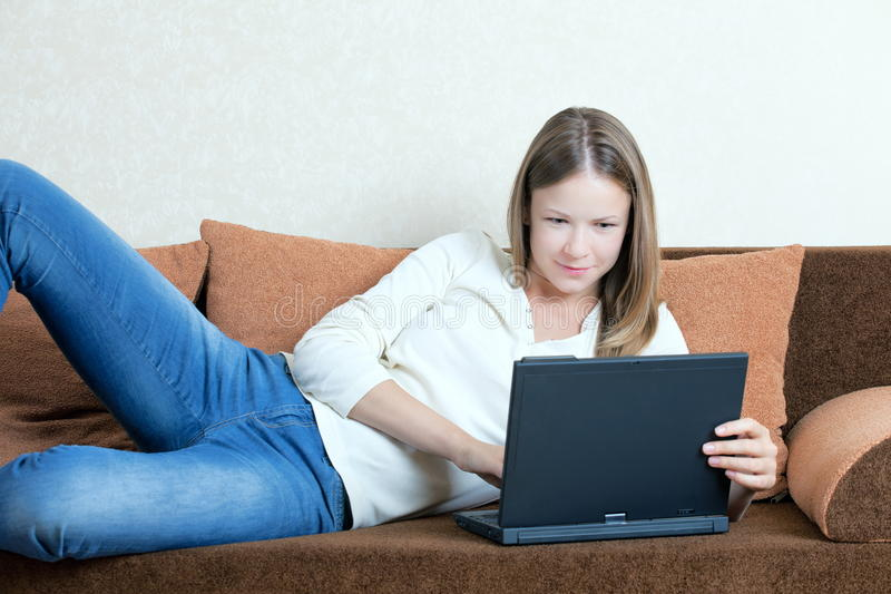 Frau mit Laptop auf dem Sofa stockfotos