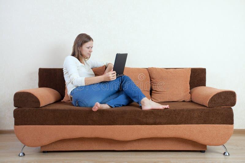 Frau mit Laptop auf dem Sofa lizenzfreies stockbild