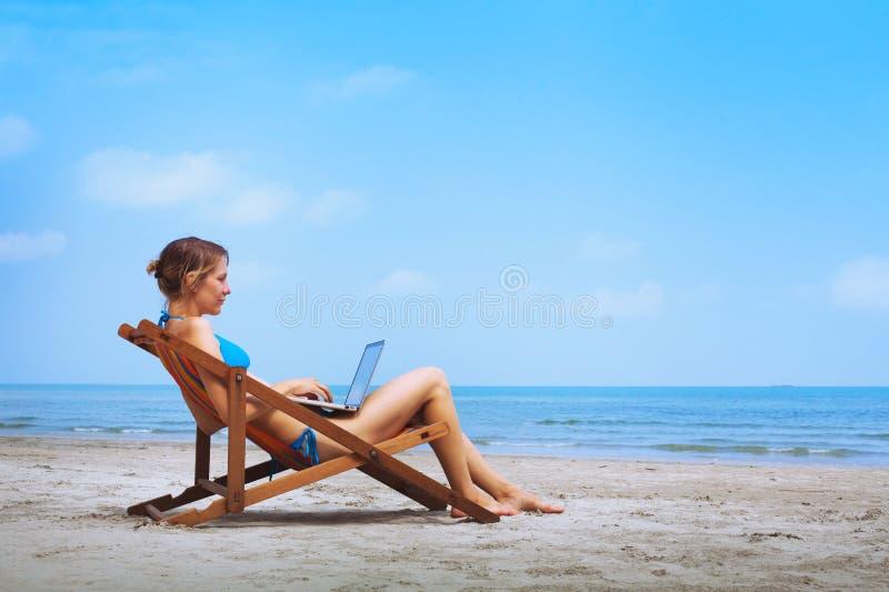 Frau mit Laptop auf dem Strand stockfotos