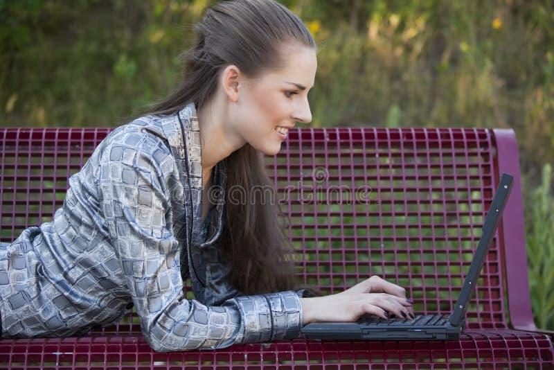 Frau mit Laptop auf der Bank stockfotografie