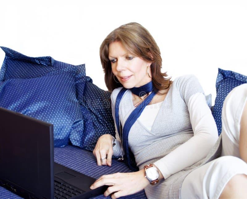 Frau mit Laptop auf Sofa stockfoto