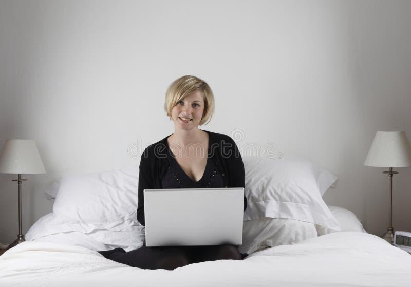 Frau mit Laptop im Bett lizenzfreie stockfotos