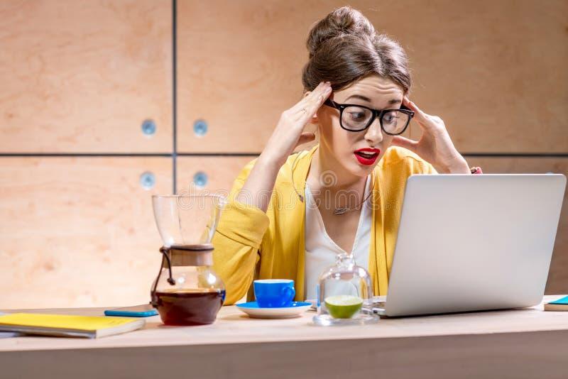 Frau mit Laptop im hölzernen Innenraum lizenzfreie stockbilder