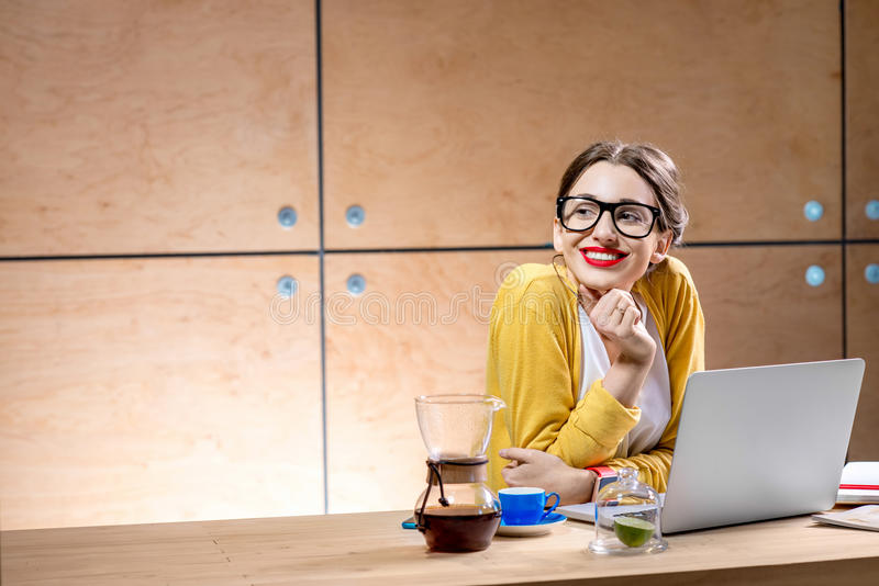 Frau mit Laptop im hölzernen Innenraum stockfotografie