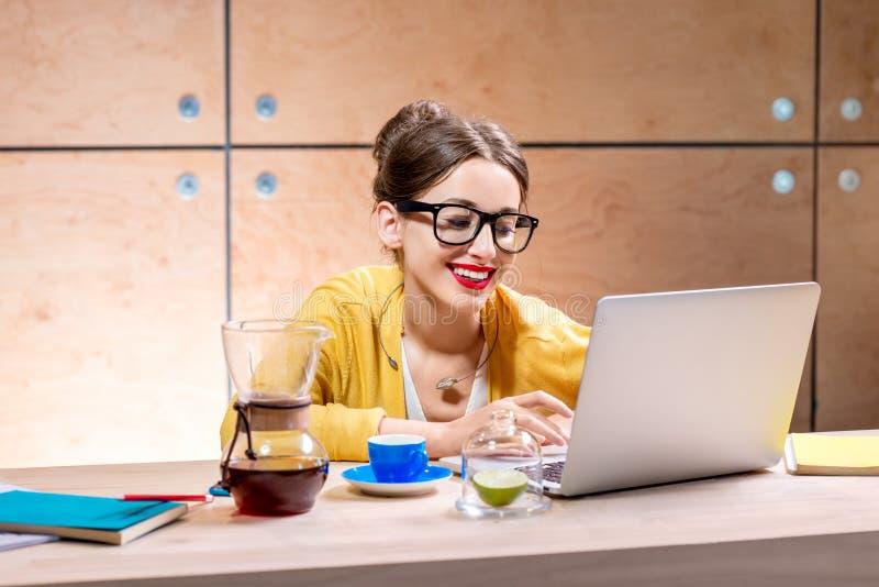 Frau mit Laptop im hölzernen Innenraum stockbilder