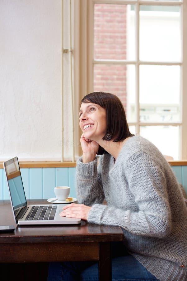 Frau mit Laptop träumend stockfotografie