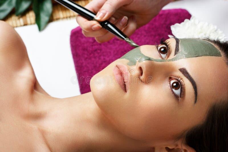 Frau mit Lehmgesichtsschablone im Sch?nheitsbadekurort Skincare Makrodetail des kosmetischen Beh?lters voll echter Perlen ?ber Hi lizenzfreie stockfotografie