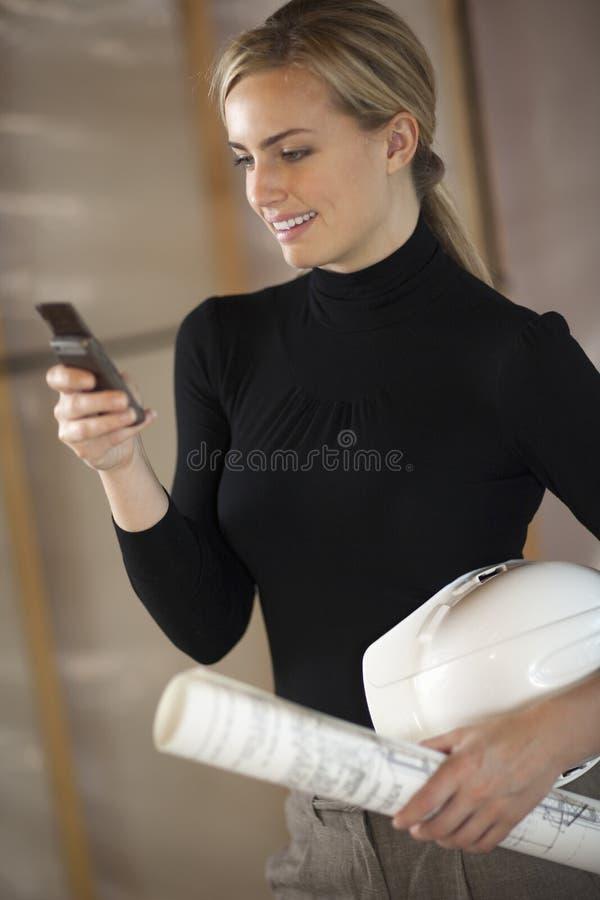 Frau mit Lichtpausen, Hardhat und Handy stockfotos