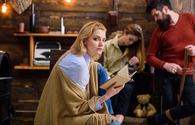 Frau mit müdem Blicklesebuch Blonde Frau im blauen Hemd und in den Jeans wickelte die woolen umfassende genießende Glättung mit e lizenzfreie stockfotos