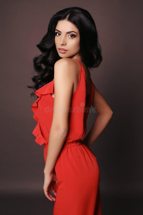 Frau mit Make-up des dunklen Haares und des Abends, trägt elegantes rotes Kleid stockfotografie