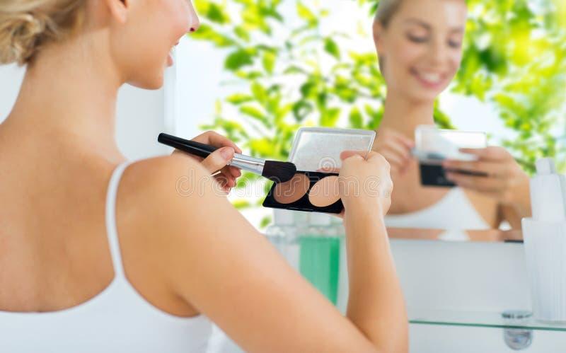 Frau mit Make-upbürste und Grundlage am Badezimmer lizenzfreies stockfoto