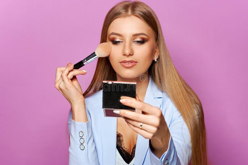 Frau mit Make-upbürste und -spiegel lizenzfreie stockfotos