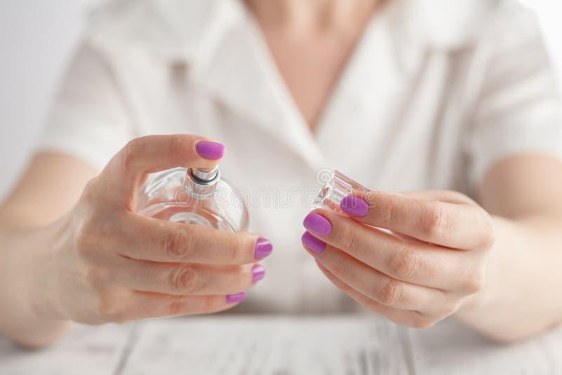 Frau mit Maniküre hält eine Flasche Parfüm lizenzfreie stockfotografie