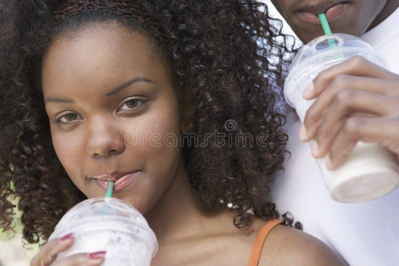 Frau mit Mann-nippendem Milchshaken stockfotografie