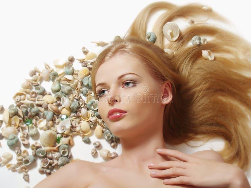 Frau mit Marinecockleshell im Haar stockfoto