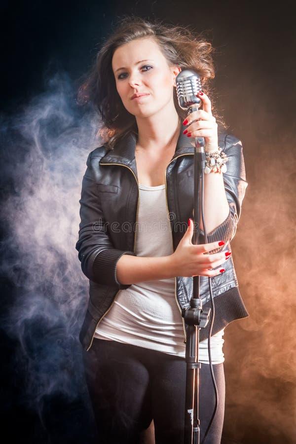Frau mit Mikrofon auf der Stufe stockfotografie