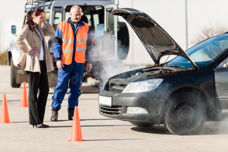 Frau mit Motor des rauchenden Autos der Technikerhilfe stockfotografie