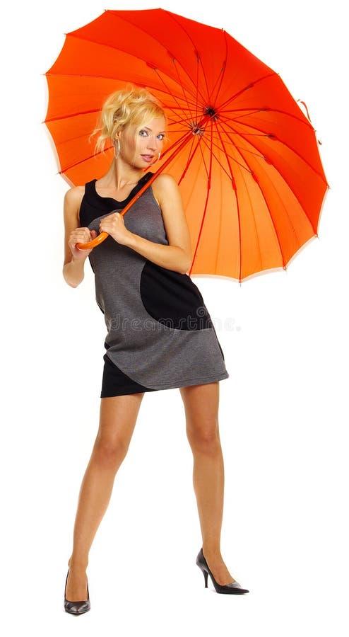 Frau mit orange Regenschirm lizenzfreie stockbilder